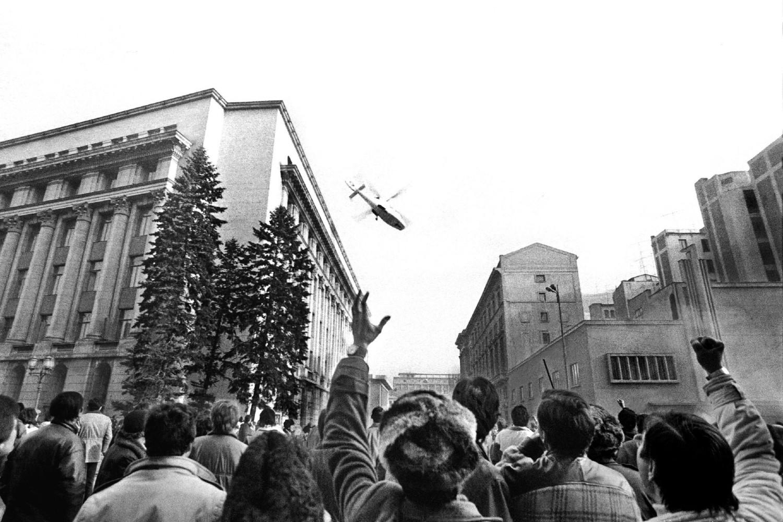 Ljudi posmatraju odlazak helikoptera iz sedišta Centralnog komiteta Rumunske komunističke partije u kom se nalazi bračni par Čaušesku, Bukurešt, 22. decembar 1989. (Foto: Reuters/Lucian Crisan)