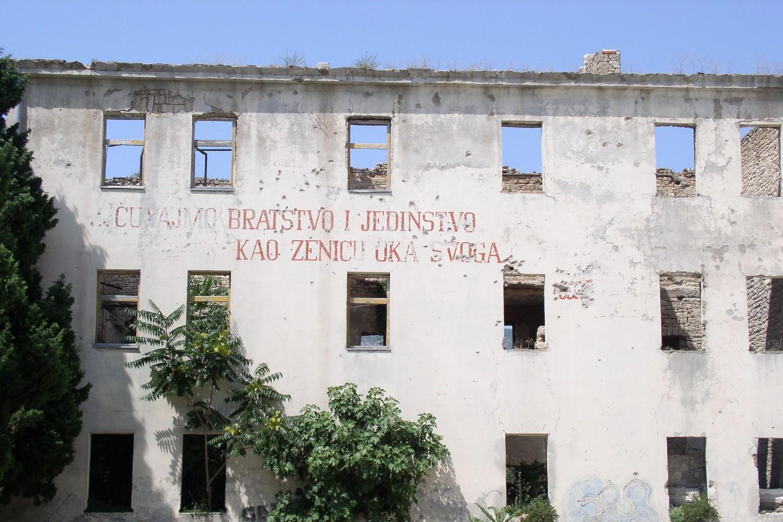 """Zgrada bivše kasarne JNA u Mostaru sa natisom – """"Čuvajmo bratstvo i jedinstvo, kao zjenicu oka svog"""" (Foto: Wikimedia/Antidiskriminator, CC BY-SA 3.0)"""