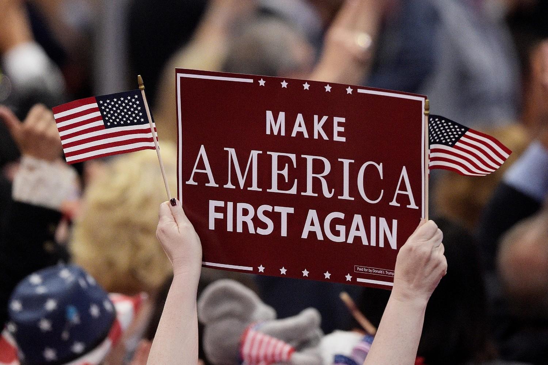"""Trampove pristalice sa američkim zastavicama i transparentom na kome piše """"Amerika na prvom mestu"""" tokom otvaranja trećeg dana Republikanske nacionalne konvencije, Klivlend, 20. jul 2016. (Foto: Jeff Swensen/Getty Images)"""