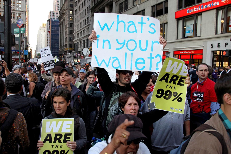 """Pripadnici pokreta """"Okupirajte Volstrit"""" sa transparentima tokom protesta u blizini Zukoti parka na Donjem Menhetnu, Njujork, 05. oktobar 2011. (Foto: AP Photo/Craig Ruttle)"""