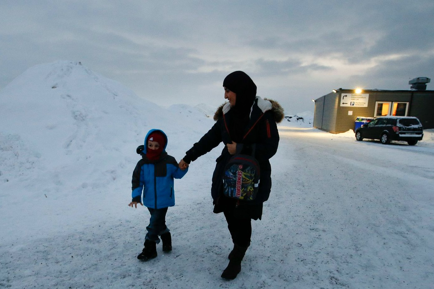 Žena migrant iz Jemena tokom šetnje sa svojim sinom ispred izbegličkog kampa u Hamerfestu, na severu Norveške, 04. februar 2016. (Foto: AP Photo/Alastair Grant)