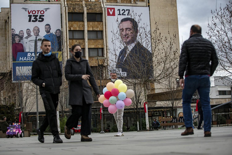 Pešaci u prolazu ispred zgrade na kojoj su okačeni predizborni plakati Aljbina Kurtija i Ramuša Haradinaja, Priština, 10. febraur 2021. (Foto: AP Photo/Visar Kryeziu)