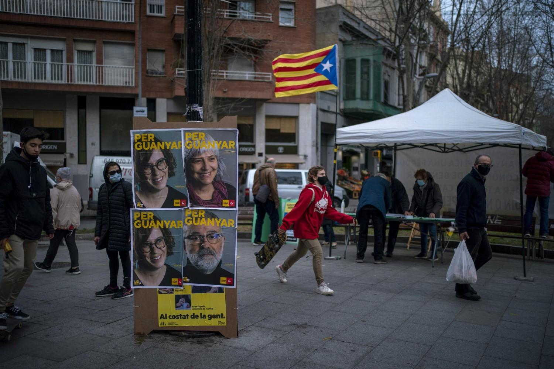 Pešaci u prolazu pored predizbornih plakata sa likovima kandidata uoči pokrajinskih izbora, Barselona, 30. januar 2021. (Foto: AP Photo/Emilio Morenatti)