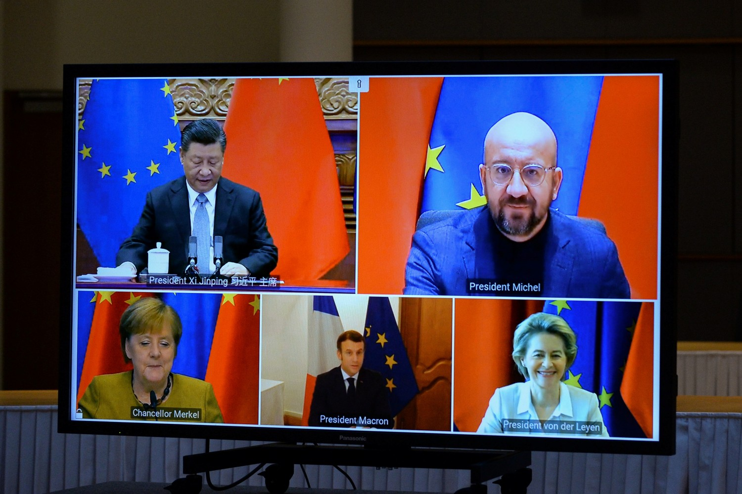 European Commission President Ursula von der Leyen, European Council President Charles Michel, German Chancellor Angela Merkel, French President Emmanuel Macron and Chinese President Xi Jinping are seen on a screen during a video conference, in Brussels, Belgium December 30, 2020. REUTERS/Johanna Geron/Pool/File Photo