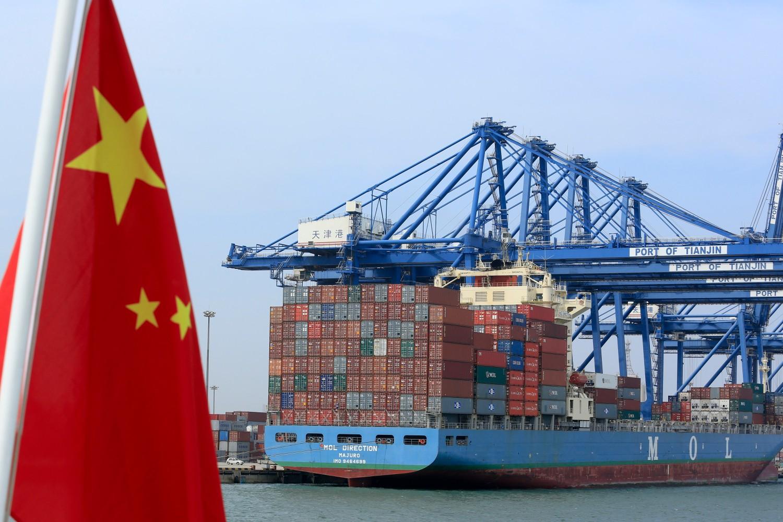 Kineska zastava nedaleko od brodskih kontejnera u luci u Tjanđinu (Kina) (Foto: Nelson Ching/Bloomberg)