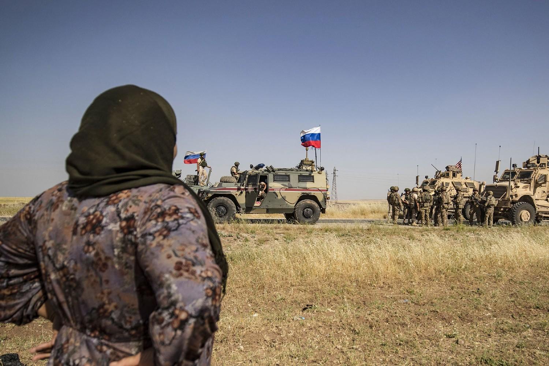 Sirijka posmatra američke i ruske vojnike u severoistočnom gradu Malikija, 03. jun 2020. (Foto: Delil Souleiman/AFP via Getty Images)