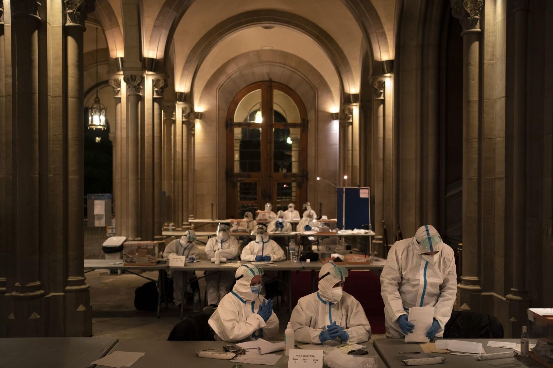 Članovi biračkog odbora u zaštitnim skafanderima tokom izbornog dana na biračkom mestu unutar Univerziteta u Barseloni, 14. februar 2021. (Foto: AP Photo/Felipe Dana)