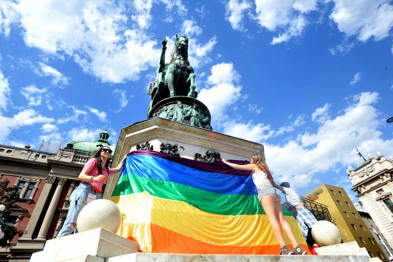Učesnice tzv. Parade ponosa kače zastavu duginih boja na spomenik knezu Mihailu na Trgu republike u Beogradu (Foto: Tanjug/Dimitrije Goll)