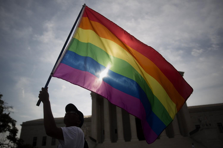 LGBT aktivista sa zastavom duginih boja ispred američkog Vrhovnog suda u Vašingtonu, 26. jun 2015. (Foto: Andrew Harrer/Bloomberg via Getty Images)