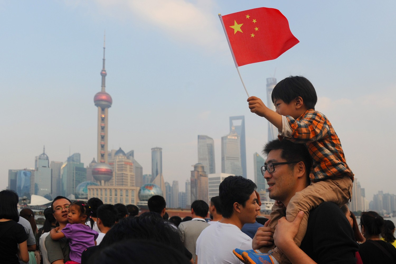 Дечак на леђима свог оца са кинеском заставом током другог дана Националног празника Кине, Шангај, 02. октобар 2014. (Фото: VCG/VCG via Getty Images)