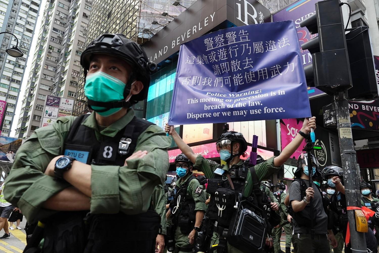 Policajci sa banerom upozorenja tokom nacionalnog praznika Kine u Hongkongu, 01. oktobar 2020. (Foto: AP Photo/Vincent Yu)