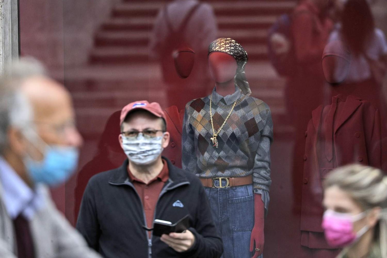 Ljudi za zaštitnim maskama na licu tokom prolaska pored jednog izloga u Rimu, 06. oktobar 2020. (Foto: AP Photo/Gregorio Borgia)