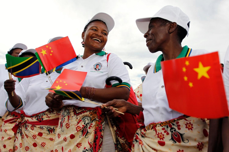 Танзанијске жене са заставицама Кине и Танзаније приликом дочека кинеског председника Сија Ђинпинга на међународном аеродрому у Дар ес Саламу, 24. март 2013. (Фото: Reuters/Thomas Mukoya)